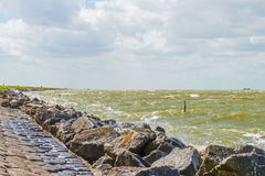 Shoreline of a stormy lake in sunlight Royalty Free Stock Photo