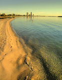 Shoreline To Buildings. Beach shoreline stretches away in the distance to tall buildings Stock Photography