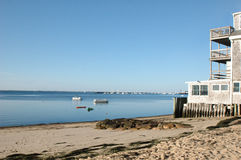 Shoreline vista of building, boats, sand and ocean Royalty Free Stock Images