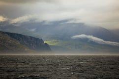 Shorescape rocoso septentrional con las colinas cubiertas con él Imagen de archivo libre de regalías