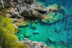 shorkling在美丽的Paleokastritsa天蓝色的海湾的岩石之间的游人在科孚岛海岛,希腊 库存照片