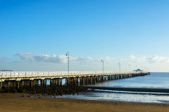 Shorncliffe Pier in early morning sun under a blue sky Royalty Free Stock Images