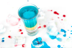 Short blue coctail with ice and color drops Stock Photography