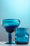 Short blue glasses. Two short blue glasses on a light blue background with purple liquid Royalty Free Stock Photography