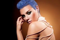 Short blue hairstyle and green makeup of female in studio Royalty Free Stock Images