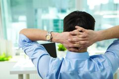 Short break. Back view of businessman having break in office stock image