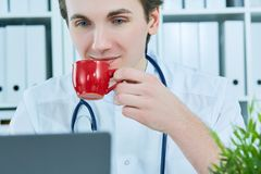 Portrait of friendly male doctor smiling holding a cup of coffee and looking at laptop screen. Short break in hard work. Portrait of friendly male doctor Royalty Free Stock Photo