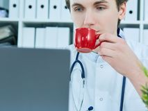 Portrait of friendly male doctor smiling holding a cup of coffee and looking at laptop screen. Short break in hard work. Portrait of friendly male doctor Royalty Free Stock Images