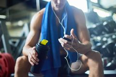 Short Break from Training. Taking short break from intensive workout: young sporty man listening to music in headphones and holding bottle with water in hand royalty free stock photography