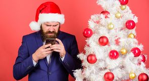 Short christmas wishes. Manager congratulate colleagues online. Read christmas greeting. Man bearded hipster wear formal. Suit and santa hat hold smartphone stock photo