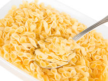 Short-cut pasta with spoon in plastic container. Stock Image