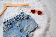 Short denim shorts on trempel on white fur and pink glasses. View from above Royalty Free Stock Image