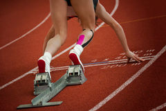 Short distance sprint start 1. Female short distance runner on gravity slope curve is in start position stock photo