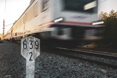 Short distance train in motion with a kilometric road sign and sunset light royalty free stock image