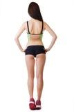 Short dos esportes da mulher desportiva bonita nova e suportes vestindo da parte superior com o seu para trás Fotos de Stock Royalty Free