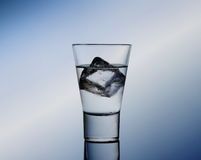 Short drink glass with clear liquid and ice cubes Stock Photo
