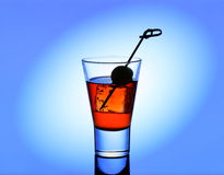 Short drink glass with red liquid and green olive Royalty Free Stock Photo