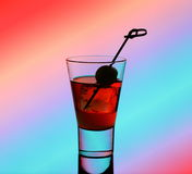 Short drink glass with red liquid and green olive Royalty Free Stock Images