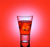 Short drink glass with red liquid and ice cubes Stock Photos