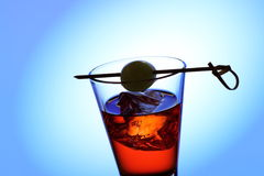 Short drink glass with red liquid, olive, ice cubes stock images