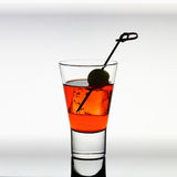 Short drink glass with red liquid, olive, ice cubes Royalty Free Stock Images