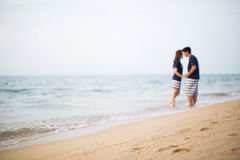 Short focus of sand beach and the couple in the background o Stock Images