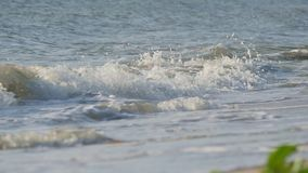 Wave and bubble hitting sandy beach late afternoon stock footage