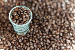 Short glass with arabica coffee beans. On blur coffee beans background. selective focus Stock Photo