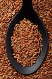 Short grain red rice. Top view of black spoon full of short grain red rice Stock Photo