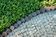 Short grass lawn and cobblestone pavement texture Royalty Free Stock Image