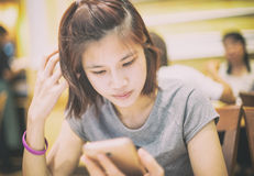 Short hair asian girl using a mobile phone in cafe. Stock Photography