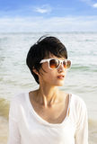 Short hair Asian woman on the beach. With sunglasses stock photography