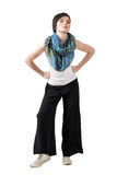 Short hair fashion model with colorful shawl and loose wide trousers posing with arms on her hips Stock Photos