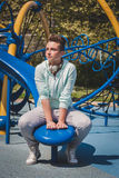 Short hair girl sitting in a children playground Stock Images