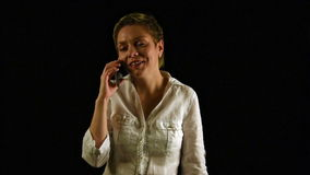 Short hair girl talking by mobile phone over black stock footage