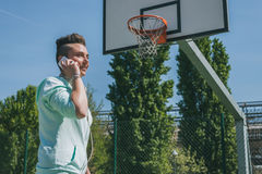 Short hair girl talking on phone in a basketball playground Royalty Free Stock Images