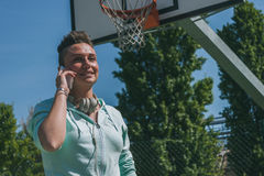 Short hair girl talking on phone in a basketball playground Royalty Free Stock Photography