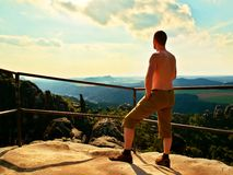 Short hair naked tourist at handrail on the peak of sandstone rock watching into landscape. Hot summer day. Stock Photo