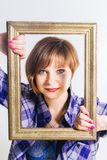 Short haired cute young Woman wearing men`s blue cotton shirt looking through frame, over white background. Close-up studio shot. stock photography