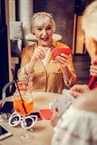 Short-haired excited old lady being in gambling mood royalty free stock images