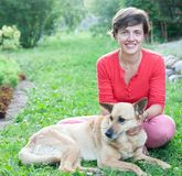 Short-haired girl sitting with   dog. Portrait of   young girl with   light dog on lawn royalty free stock photo