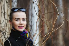 Short-haired woman in a black coat smiles among sprigs. Of spring Stock Image