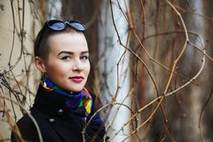Short-haired woman in a black coat smiles among sprigs of spring. Short-haired brunette woman in a black coat smiles among sprigs of spring Royalty Free Stock Photo