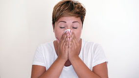 Short haired woman blowing her nose on the white background. Royalty Free Stock Photo