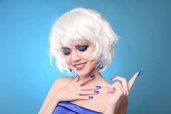 Short Hairstyle. Fun smiling blond. Makeup. Closeup of beauty fa. Shion girl with bob short hair style and glitter eyeshadow, manicured nails over blue studio royalty free stock image