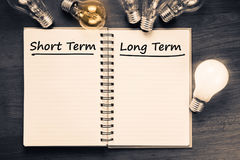 Short and Long Term Plan. Short term and Long term on opened notebook with glowing light bulb Stock Images