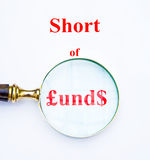 Short of money. The words Short of funds written as £und$ with pound and dollar sign . The images focuses on shortage of money by means of a hand magnifier and Stock Images