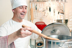 Short order cook. Man with chef hat tends to his pot Royalty Free Stock Photo