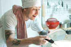 Short order cook. Man with chef hat tends to his pot Royalty Free Stock Image
