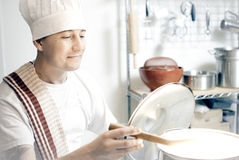 Short order cook. Man with chef hat tends to his pot Stock Photos